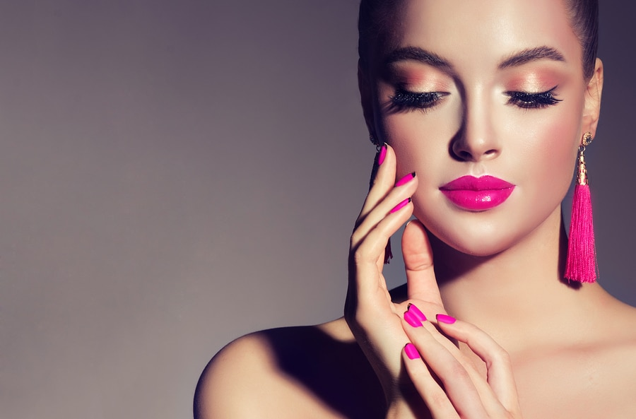 Los Angeles laser skin therapy - Beautiful model girl with pink fuchsia manicure on nails . Fashion makeup and cosmetics . Large earrings tassels jewelry Magenta color.